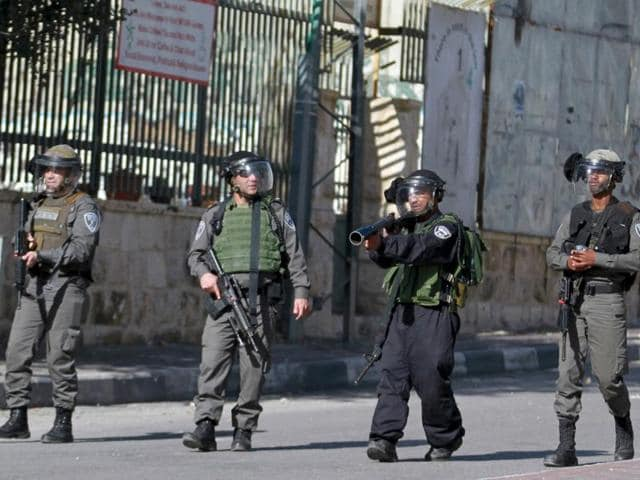 An Israeli border policeman aims his weapon towards Palestinian protesters as others take up position during clashes in the West Bank city of Bethlehem.