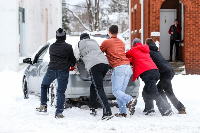 A group of friends help push a car into a safe parking spot after it was stuck on a snow-covered road in Huntington.