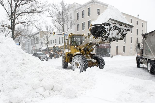 A front-end loader places snow into a dump truck, as snow falls, in Alexandria, Va.