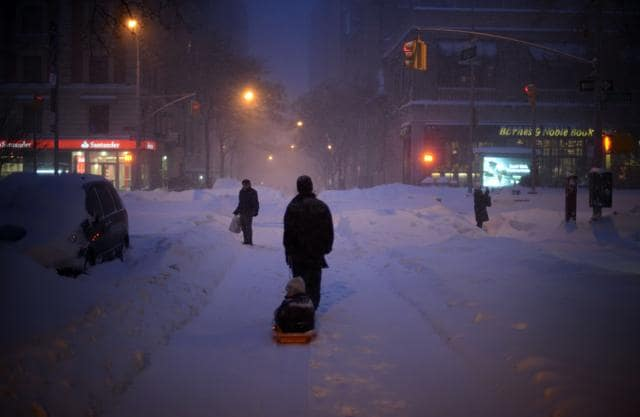 A young child is pulled home along West 82 Steet which is covered in snow after a day of constant snow fall on Sunday.