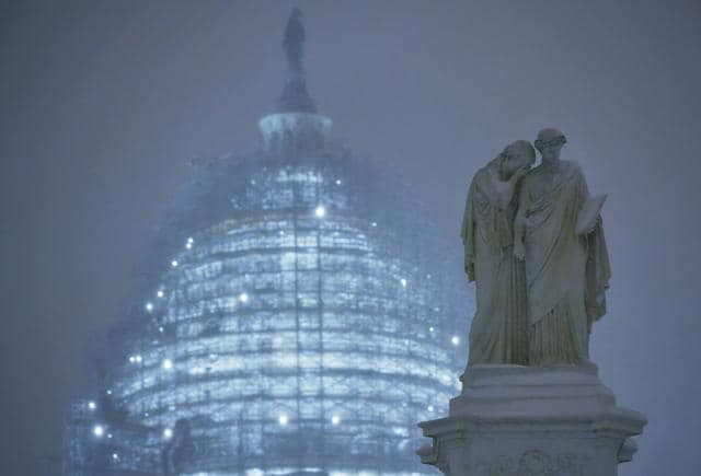 A statue is seen in front of the US Capitol in Washington, DC, as snow continues to fall on January 22, 2016.