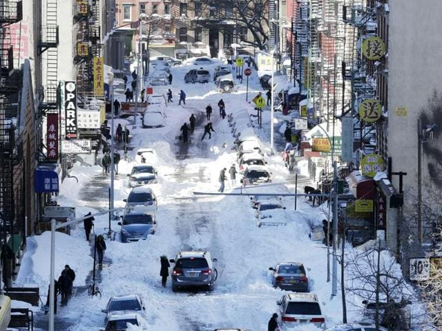 People clear snow from parked cars on Henry Street in the Chinatown neighbourhood in New York.