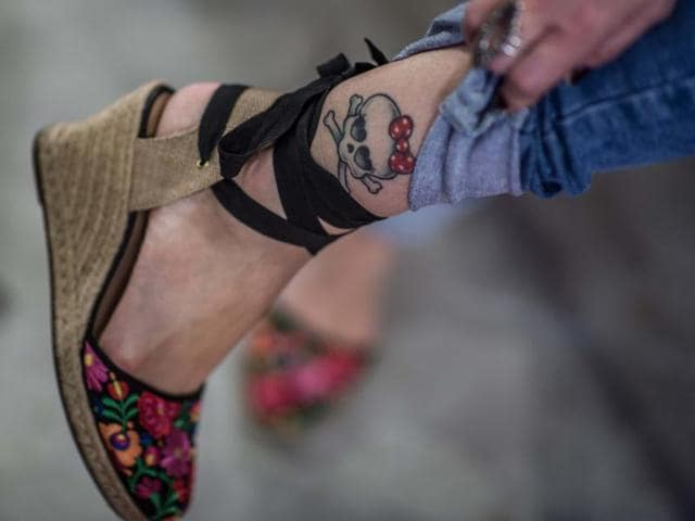 A woman shows a skull tattooed on her during the Tattoo Week internacional tattoo and piercing meeting in Rio de Janeiro, Brazil