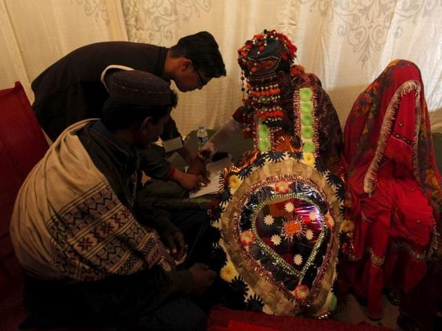 A groom signs marriage documents during a mass marriage ceremony.