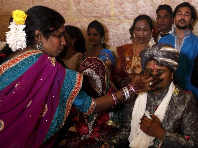 A groom receives a dot on his forehead with Sindoor (red pigment) during a mass marriage ceremony.