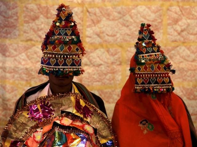 A bride and groom wearing traditional handmade garlands wait for their wedding to start in Karachi.