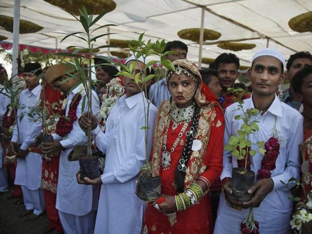 Indian muslim grooms and brides wait to plant trees to start their newly married life on a good note during a mass wedding event in Ahmadabad.