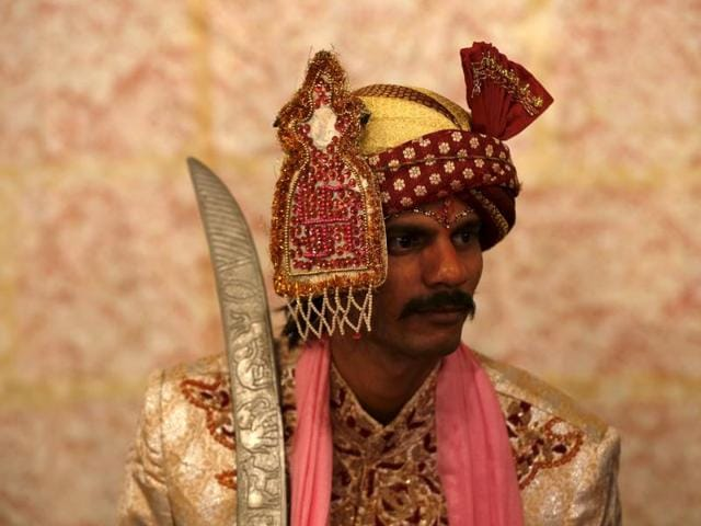 A groom in traditional dress waits for his wedding to start.