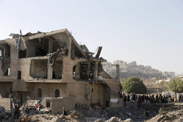 People gather outside the house of court judge Yahya Rubaid after a Saudi-led air strike destroyed it, killing him, his wife and five other family members, in Yemen's capital Sanaa on Monday.