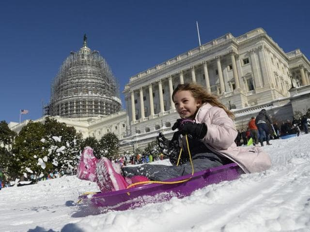A young girl is sliding on the West Lawn of the US Capitol on Saturday, in Washington.
