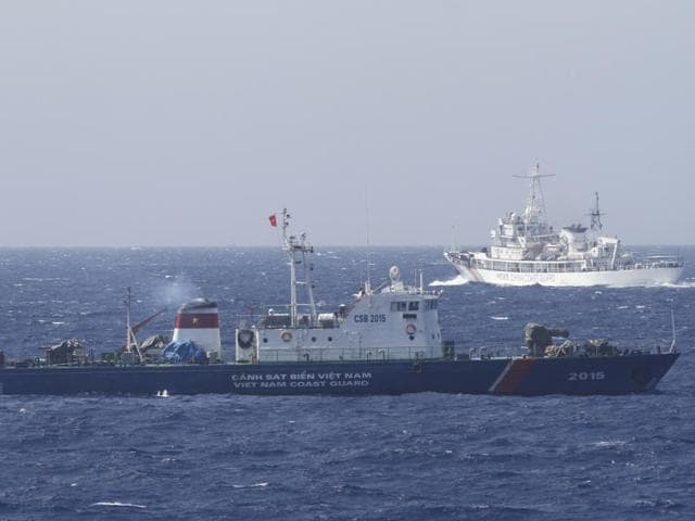 A file photo of a ship (top) of the Chinese Coast Guard  seen near a ship of the Vietnam Marine Guard in the South China Sea, about 210 km  off the shore of Vietnam.