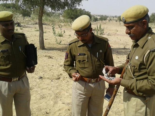 Police officials examine the remains of a balloon-shaped object which was shot down by an IAF fighter jet in Barmer on Tuesday.