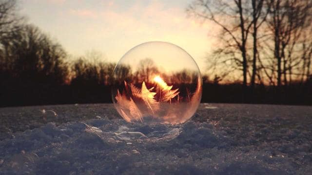 """These stunning snapshots of delicate frozen bubbles will take your breath away. The beautiful photos show intricate crystals forming on the delicate bubbles that look like snowflakes, lit up by the rising sun. The striking pictures were taken by photographer Michelle Lynn Fritz, from Pennsylvania, USA, in her back garden. Michelle, 49, said: """"Photographing frozen bubbles is very tricky – it is almost essential that there's no wind and the temperatures need to be below freezing. She adds, """"I love the way the colours and patterns are illuminated by the sunlight. """"Many have said they remind them of snow globes – tiny little worlds of beauty."""""""