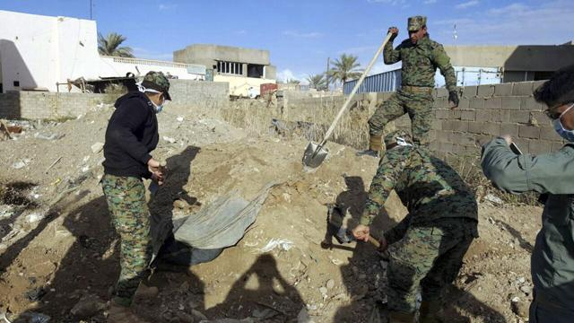 Iraqi security forces members work at the site of a mass grave grave believed to contain the bodies of Iraqi civilians killed by Islamic State group militants in Ramadi, 115 kilometers (70 miles) west of Baghdad.(AP Photo)