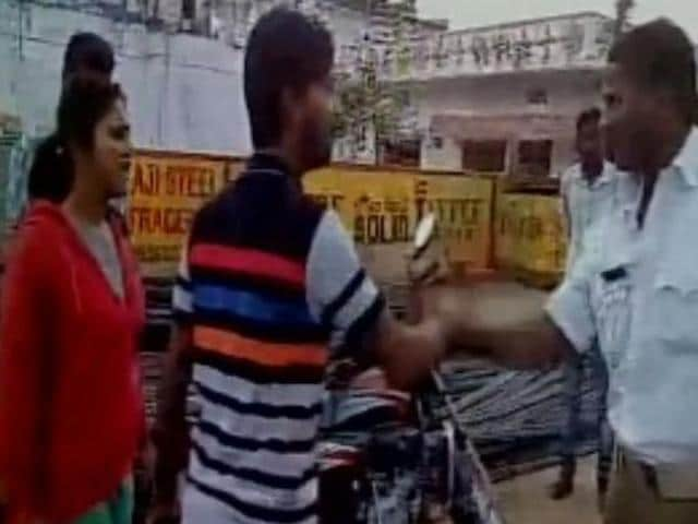 Two students have been booked for assaulting a traffic cop after they were stopped for allegedly violating the traffic rules
