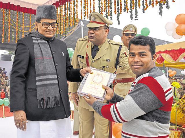 Daily wage labourer Deepak Kumar receives a memento from Rajya Sabha MP Ram Gopal Yadav at the function at the Harsaon police lines on Tuesday.