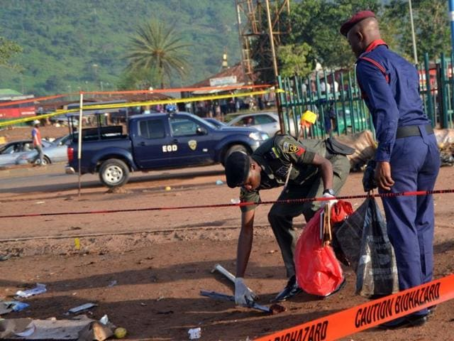Nigerian bomb experts collect clues from a bomb blast site for analysis in Nyanya, near Abuja.(AFP File Photo)
