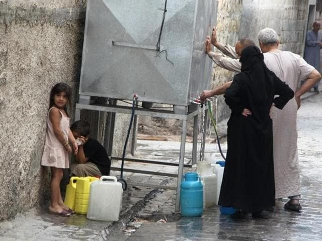 Residents fill water containers in Aleppo, Syria.