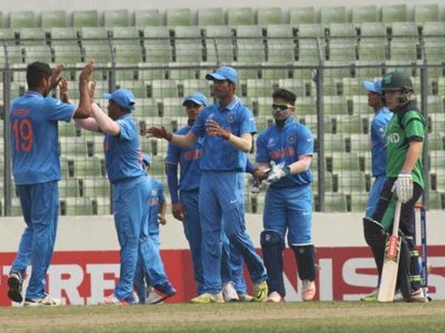 Indian players celebrate the fall of an Irish batsman's wicket. India won by 79 runs