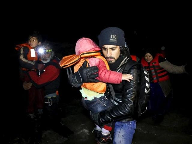 An Afghan migrant carries a child as he arrives with other Afghan migrants on a raft on the Greek island of Chios.