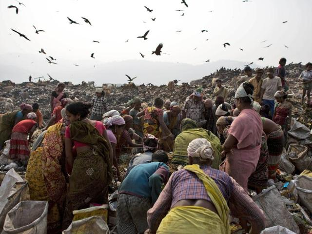 In this file photo, scavengers crowd around a fresh load of garbage dumped by a collection truck in Guwahati.
