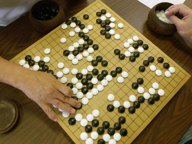 Go, which originated in China more than 2,500 years ago, involves two players who take turns putting markers on a checkerboard-like grid.