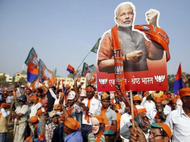 A supporter of Bharatiya Janata Party holds up a cutout of Prime Minister Narendra Modi during an election campaign rally in Varanasi, Uttar Pradesh.(AP File Photo)