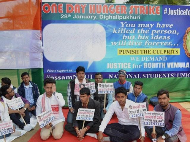 Student holds a banner and a photograph of Rohith Vemula, as he sits with others during a hunger strike to demand justice in Hyderabad.