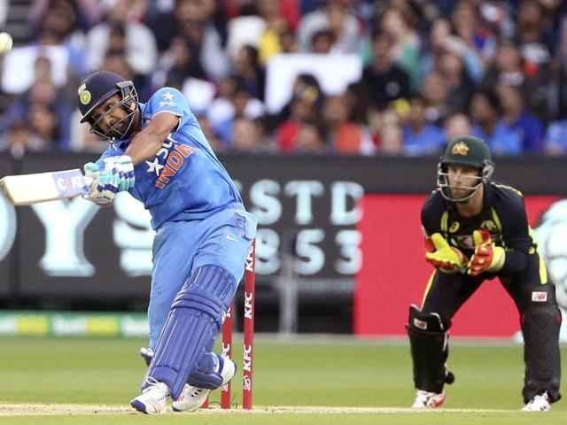 India's Rohit Sharma (L) hits a six while batting as Australia's Matthew Wade watches during their T20 cricket match at the Melbourne Cricket Ground on January 29, 2016.