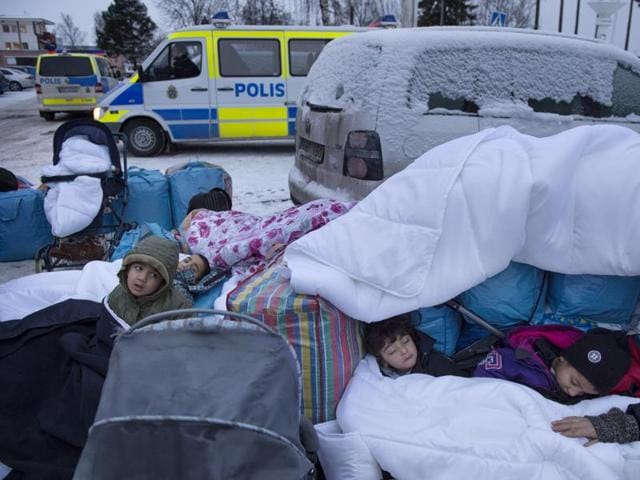 Children Nor, Saleh and Hajaj Fatema from Syria sleep outside the Swedish Migration Board in Marsta, outside Stockholm, Sweden. Dozens of masked men assaulted migrants in the Swedish capital on Friday amid rising tension over immigration.