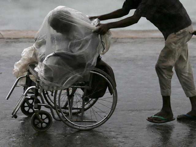 A man pushes a wheelchair with a disabled man, who is sheltered from the rain with a plastic cover in Colombo. Several Sri Lankans suggested that their country's welfare measures are responsible for its civic sense.