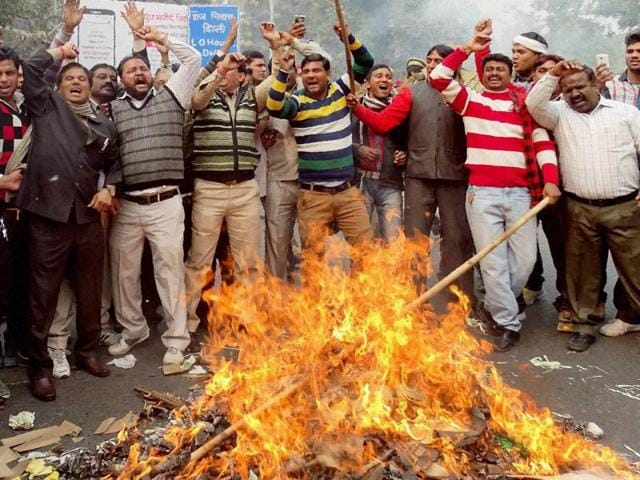 MCD workers burning effigies during a protest over non-payment of salaries, at Civil Lines in New Delhi.