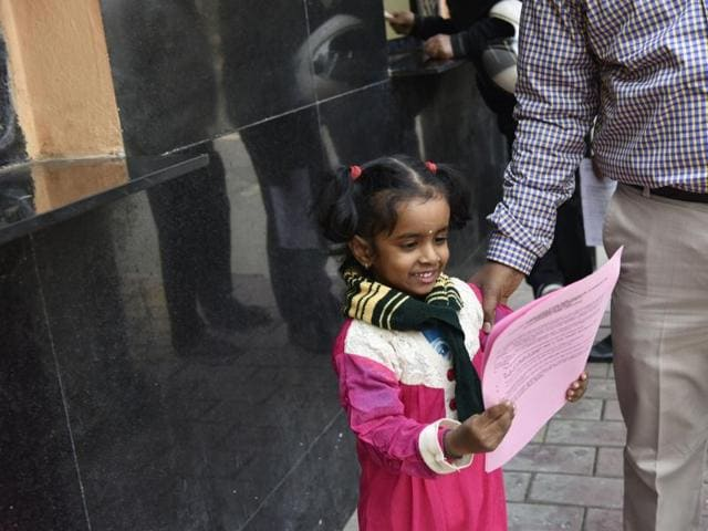 Parents buy admission forms for nursery for their children at a school in New Delhi.