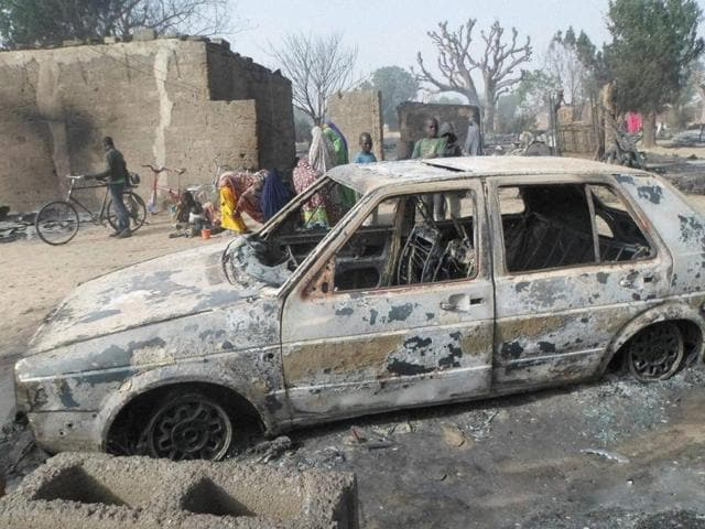 Children gather around a burnt out car following an attack by Boko Haram in Dalori village 5 kilometers from Maiduguri, Nigeria.