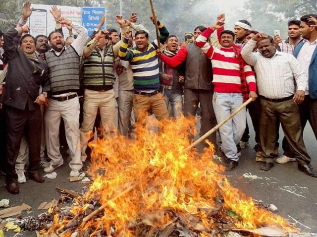 MCD workers burning effigies during a protest over their demands at Civil Lines in New Delhi on Friday.