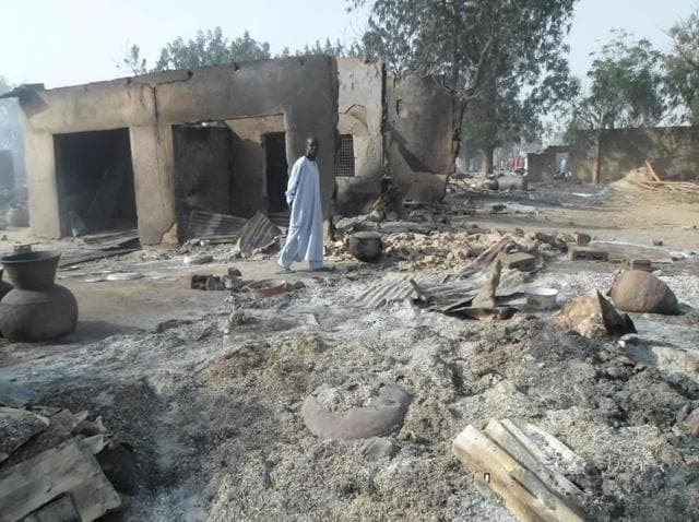 A man walks past burnt out houses following an attack by Boko Haram in Dalori village in Nigeria.