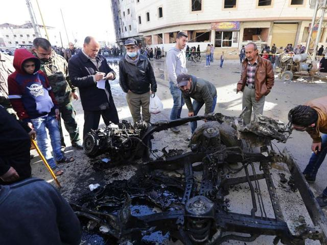 Syrians look at the wreckage of a vehicle at the site of suicide bombings in the area of a revered Shiite shrine in the town of Sayyida Zeinab.