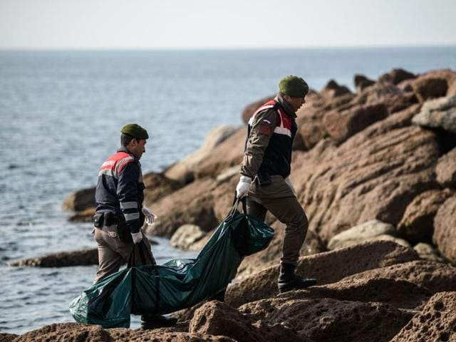 Turkish gendarmes carry the body of a migrant who washed up on a beach in Canakkale's Bademli district on January 30, 2016.