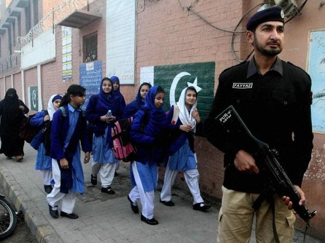 A police officer stands guard as children make their way to school in Lahore.