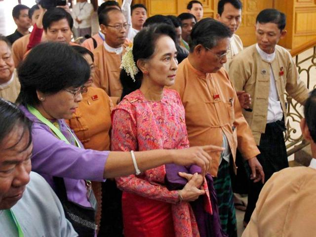 Aung San Suu Kyi walks along with other lawmakers of her National League for Democracy party as they leave after a regular session of the lower house of Parliament.