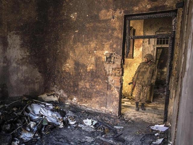 In this file photo, a Pakistani army soldier inspects a classroom of the Peshawar school which was attacked by the Taliban militants.