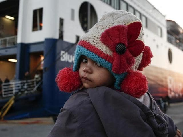A baby in front of a ferry at the port of Piraeus near Athens, Sunday, Jan. 31, 2016. Over one million migrants and refugees, many fleeing the Syria conflict, crossed into Europe last year.