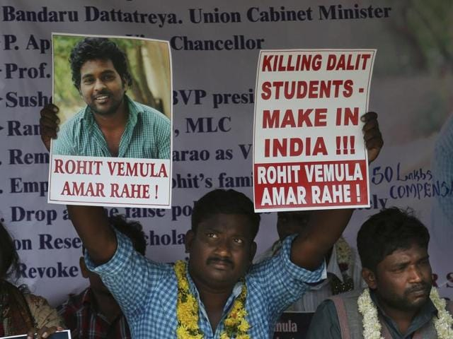 A student holds a banner and a photograph of Rohith Vemula, as he sits with others during a hunger strike to demand justice in Hyderabad.