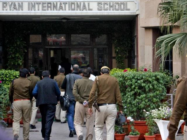 Police officials enter the premises of Ryan International School where a six-year-old student was found dead in a pit.