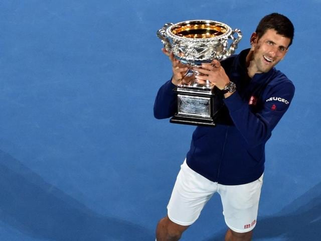 Serbia's Novak Djokovic holds the trophy as he celebrates after victory in his men's singles final against Britain's Andy Murray on day fourteen of the 2016 Australian Open tennis tournament in Melbourne on January 31, 2016.