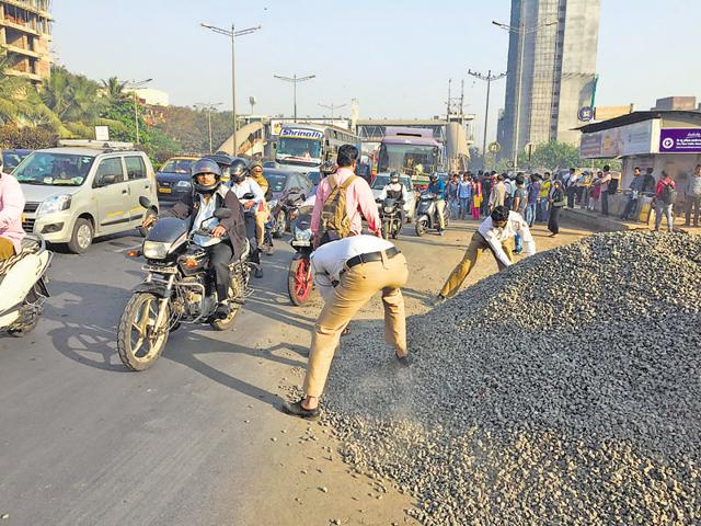 Traffic constables manually remove the pile of gravel from the spot at Jogeshwari (East) on Monday.