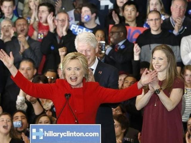 Former US President Bill Clinton (rear) applauds his wife, Democratic US presidential candidate Hillary Clinton, as they appear with their daughter Chelsea (R) at a caucus rally in Des Moines, Iowa.