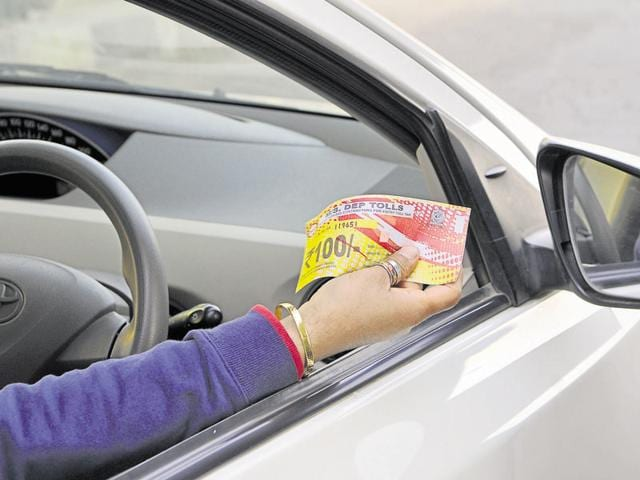 A cab driver displays the new Rs 100 toll pass.