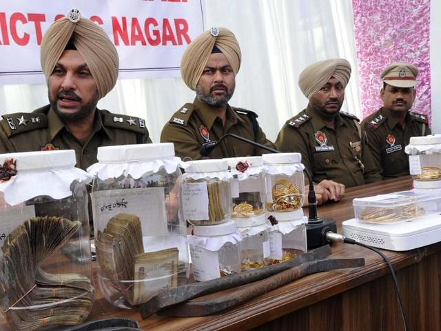 SASNagar  senior superintendent  of police  Gurpreet Singh Bhullar (extreme left) showing cash and jewellery recivered from the accused in Mohali on Monday.