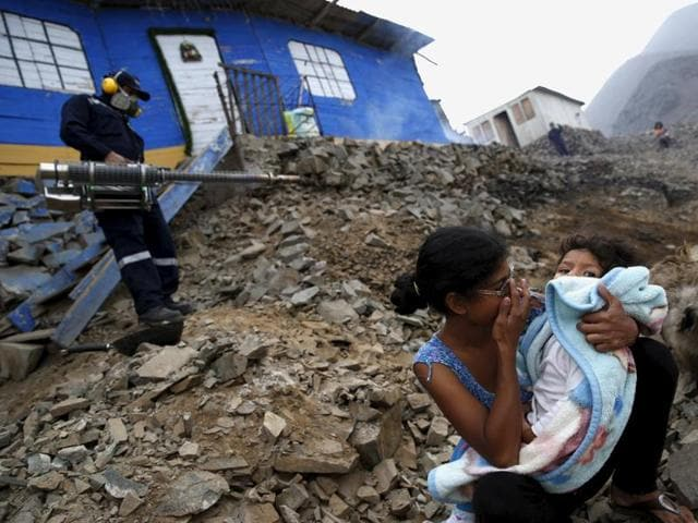 A health worker fumigates a house as residents wait outside during a campaign against the Zika virus and other mosquito-borne diseases at Carabayllo in Peru.